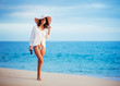 Beautiful young woman walking on tropical beach