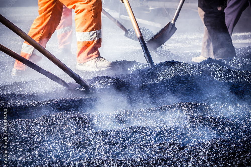 Fototapeta Workers making asphalt with shovels at road constructio