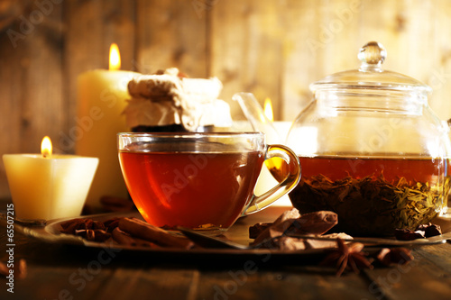 Composition with tea in cup and teapot and candles - 65507215