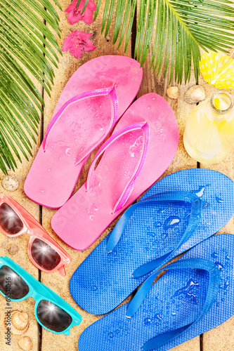 Beach, palm tree leaves, sand, sunglasses and flip flops