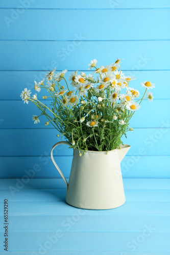 Foto op Canvas Madeliefjes Chamomiles in jug on color wooden background