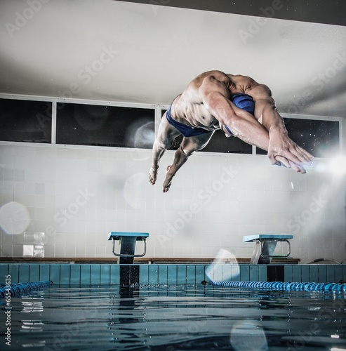 Fotografía  Young muscular swimmer jumping from starting block