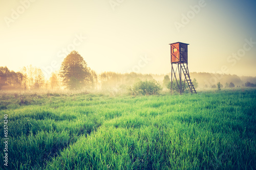 Poster Chasse vintage sunrise over meadow with raised hide