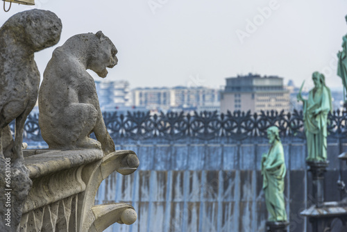 Fotografia  Angels facing gargoyles on top of Notre-dame Cathedral