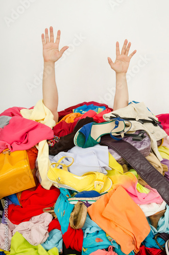 Fotografie, Obraz Man hands reaching out for help from a big pile of woman clothes