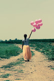 Young woman holding pink balloons and walking in a meadow. Photo - 65684063