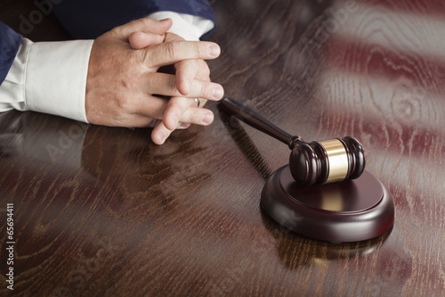 Fotografering  Judge Rests Hands Behind Gavel with American Flag Table Reflecti
