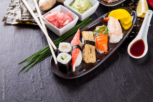 Delicious sushi pieces served on black stone
