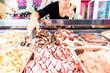 canvas print picture - Eisverkäuferin portioniert Kugel Eiscreme in Waffel