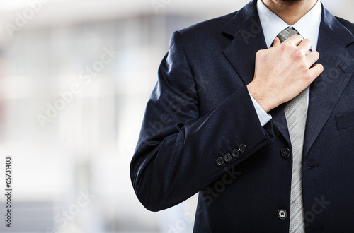 Fotografie, Obraz  Businessman adjusting his necktie