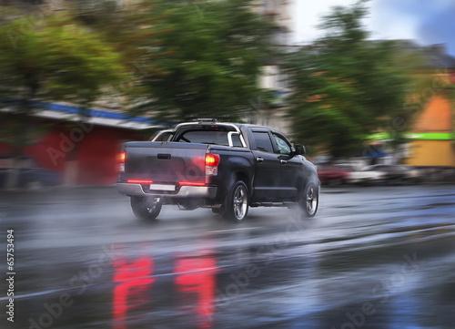 Obraz pickup goes on the rainy city street - fototapety do salonu
