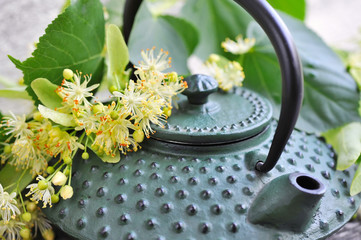 Obraz na płótnie Canvas Teapot with linden tea and flowers, close-up
