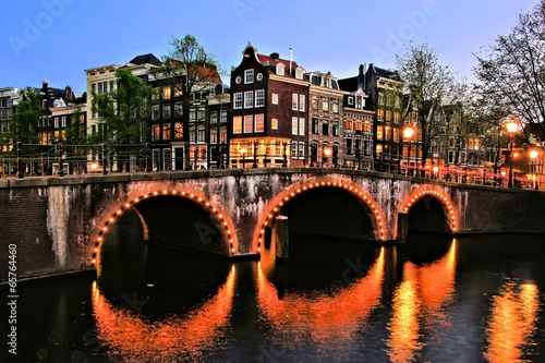 Canal houses of Amsterdam with bridge lit at night, Netherlands Canvas Print