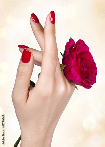 Red manicure on a woman's hand with red roses. Poster