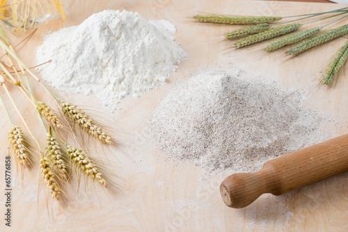 Obraz na plátně Farine bianche e spighe di grano su un asse di legno
