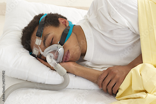 young  man  sleeping with apnea and CPAP machine Canvas Print