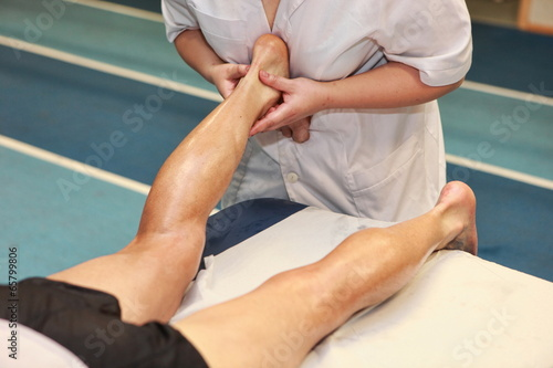 Photo masseuse massaging athlete' s Achilles tendon after running