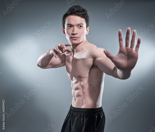 фотографія  Muscled asian kung fu man in action pose. Blood stripes on his c