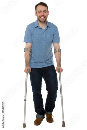 Fotografia Smiling young man using crutches