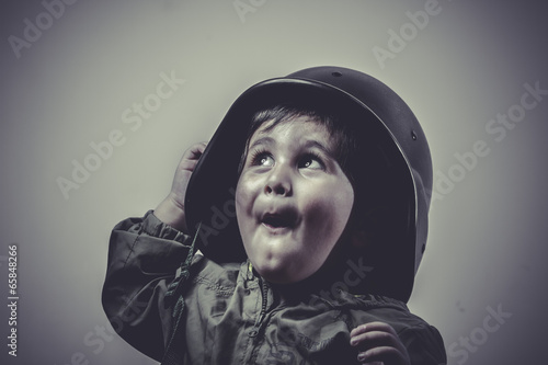 Photo  soldier fun and funny child dressed in military cap, playing war