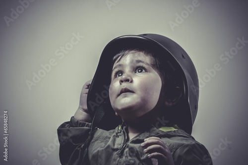 Photo  fighter, fun and funny child dressed in military cap, playing wa