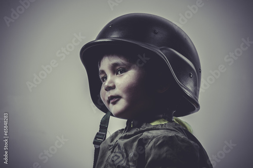 Photo  fun and funny child dressed in military cap, playing war games