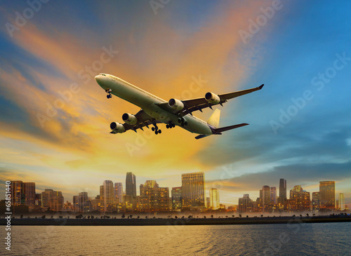 Fototapety, obrazy: passenger plane flying above urban scene use for convenience air