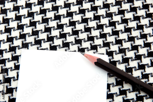 Photo  White note pad and pencil on  houndstooth pattern cotton.
