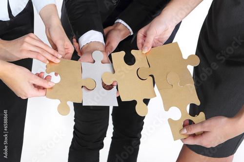 Grupa ludzi prezentuje srebrno złote puzzle - fototapety na wymiar