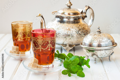 Papiers peints Maroc Moroccan tea with mint and sugar in a glass on a white table