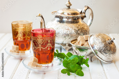 Fotografía  Moroccan tea with mint and sugar in a glass on a white table