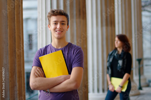 Photo Smiling teenage student outdoors with a girl at the background