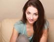 Fun beautiful girl sitting on the sofa at home