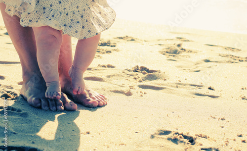 Fotografía  mother and baby feet at the beach sand