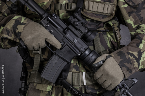 Fotografia  Detail of a soldier holding modern weapon M4