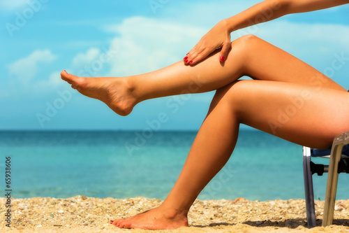 Photo  Close up of a female legs at the beach.