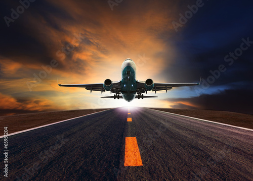 passenger jet plane flying over airport runway against beautiful Canvas Print