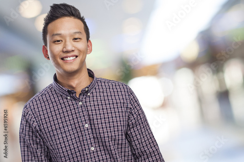 Foto  Handsome young asian man smiling wearing a plaid shirt