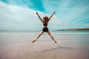 Fototapeta samoprzylepna Young woman doing star jumps on the beach