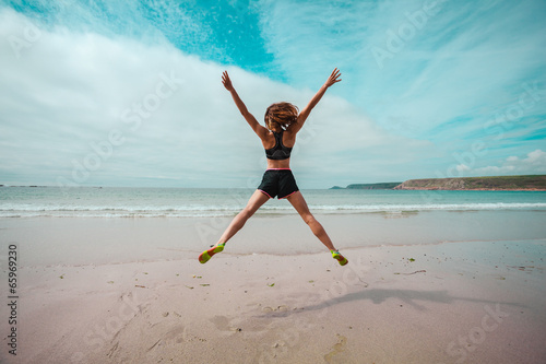 Young woman doing star jumps on the beach Canvas Print