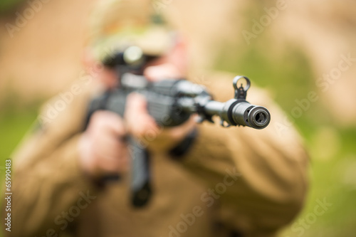 Photo  Man in camouflage with a shotgun aiming at a target. Focus on ho