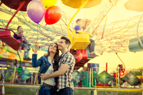 Foto op Plexiglas Amusementspark Young couple hugging in amusement park