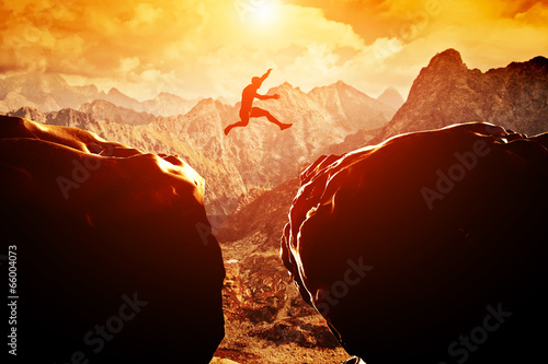 Fotografía  Man jumping over precipice between two mountains at sunset