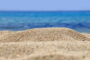 Sandy beach closeup with blur blue sea behind