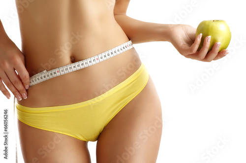 Fotografie, Obraz  Close up of a woman showing hips with a fruit in her hand