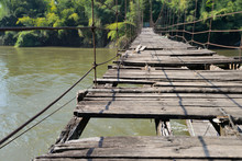 Very Old Hanging Footbridge Across River.