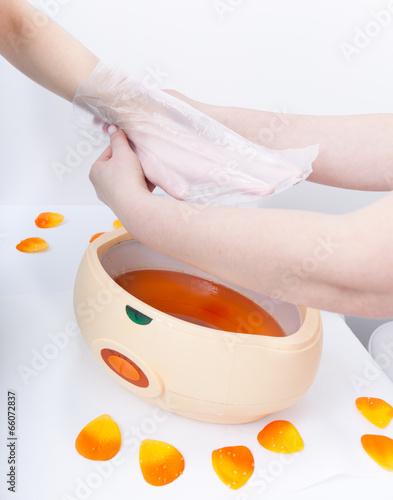 Fotografia Hand orange paraffin wax in bowl. Manicure beauty spa salon