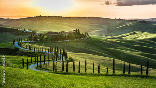Fotobehang Toscane Sunset over the winding road with cypresses in Tuscany