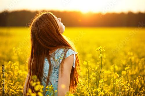 Fotografia  Young woman enjoying sunlight in canola field
