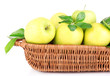 Ripe sweet apples with leaves in wicker basket, isolated